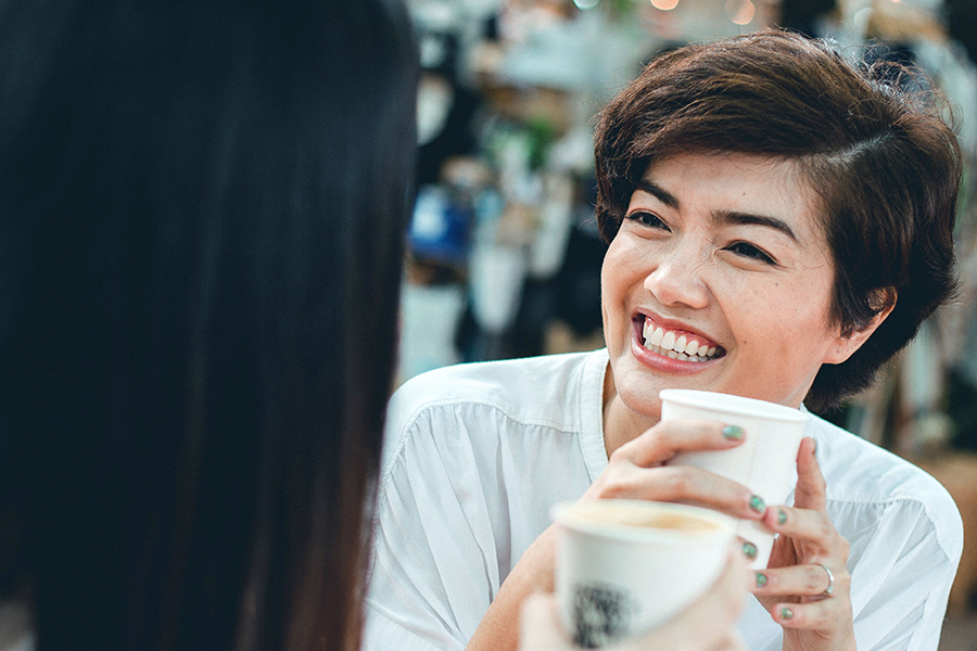 Person smiling and holding coffee cup while talking to someone.